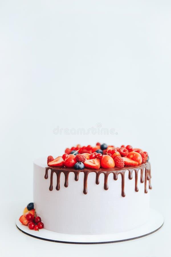 Cake met witte die kaasroom, met ganache en rode bessen op een witte tribune wordt verfraaid royalty-vrije stock foto's