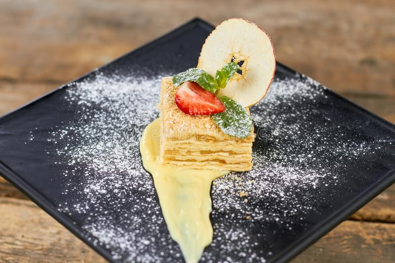 Cake Napoleon of puff pastry with sour cream on a black plate. stock images