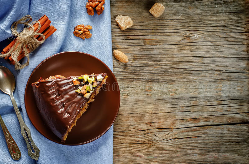 Cake with nuts, chocolate chips and chocolate glaze. On dark wood background. tinting. selective focus royalty free stock photos