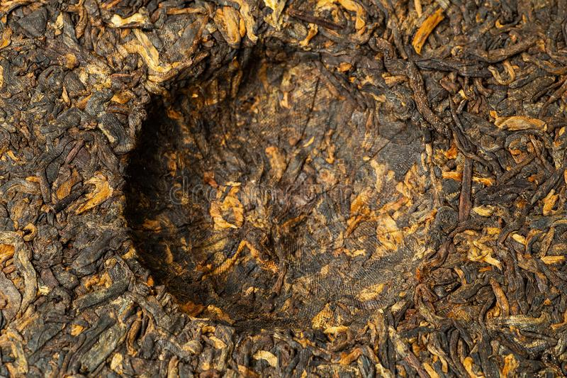 Cake of old Chinese Black tea Shu pu-erh or puer, traditional asian drink, macro, top view royalty free stock photography