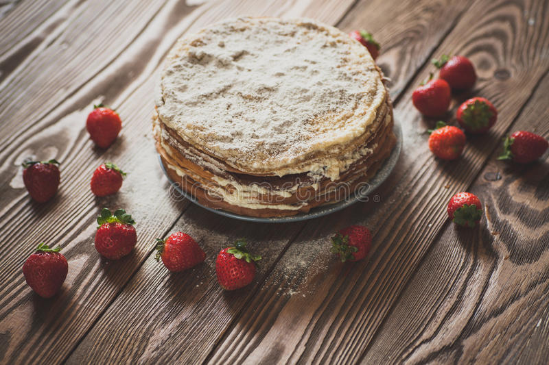Cake of pancakes,top view dark brown wooden background, rustic. Cake of the pancakes, cake with strawberry top view of a dark brown wooden background, rustic stock photography