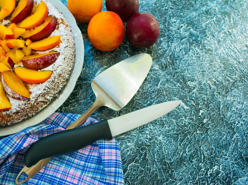 Biscuit cake with peaches and plums on a textural black background. Cooking dissert. Copy space. Cake with peaches and plums on a textural black background royalty free stock images