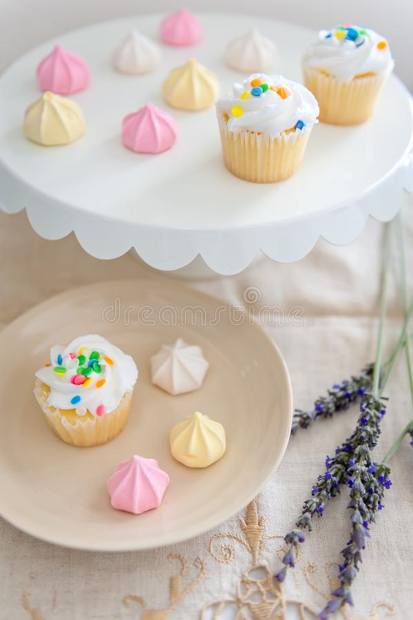 A cake plate and dessert plate filled with confetti sprinkled cupcakes and pastel colored meringue bite cookies. royalty free stock photo