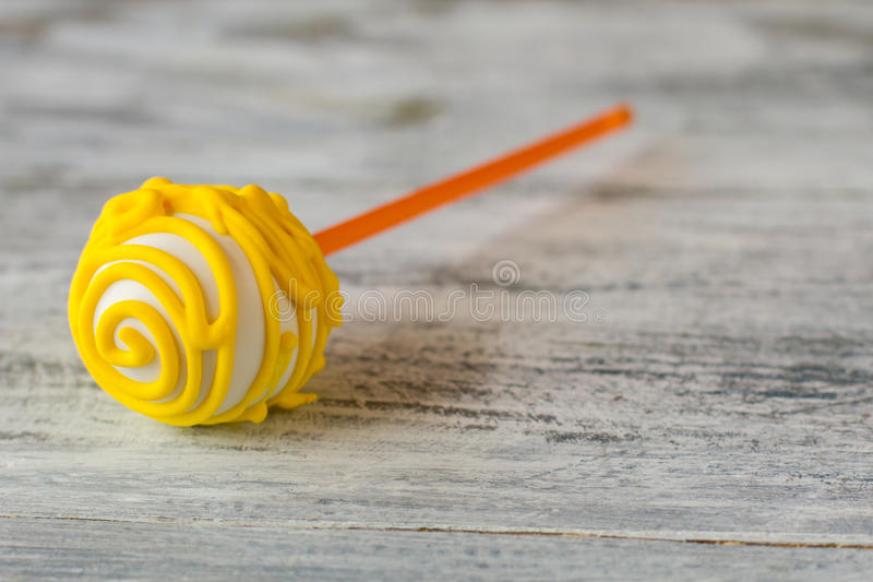 Cake pop with yellow icing. Candy lying on gray surface. Proven recipe of good mood. Sweeten up your day stock photography