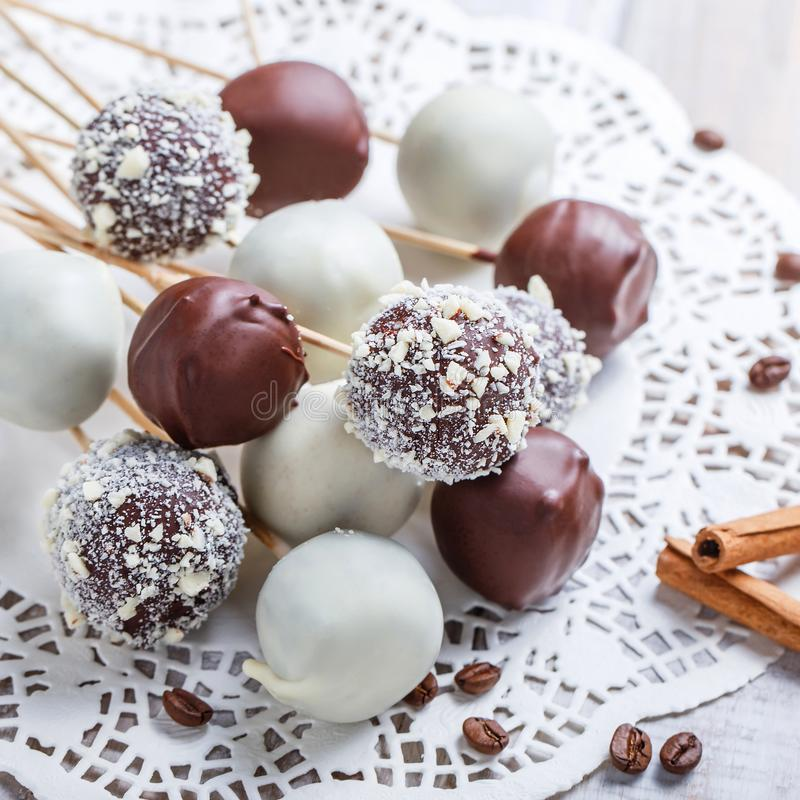 Cake pops decorated with white, dark chocolate and coconut on napkin, natural light selective focus. Cake pops decorated with white, dark chocolate and coconut stock photography