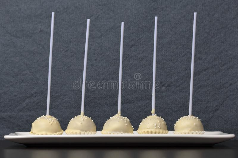 Cake pops in white chocolate glaze. Stand vertically on a stand. Decorated with white decorative sprinkles. On a gray background stock images