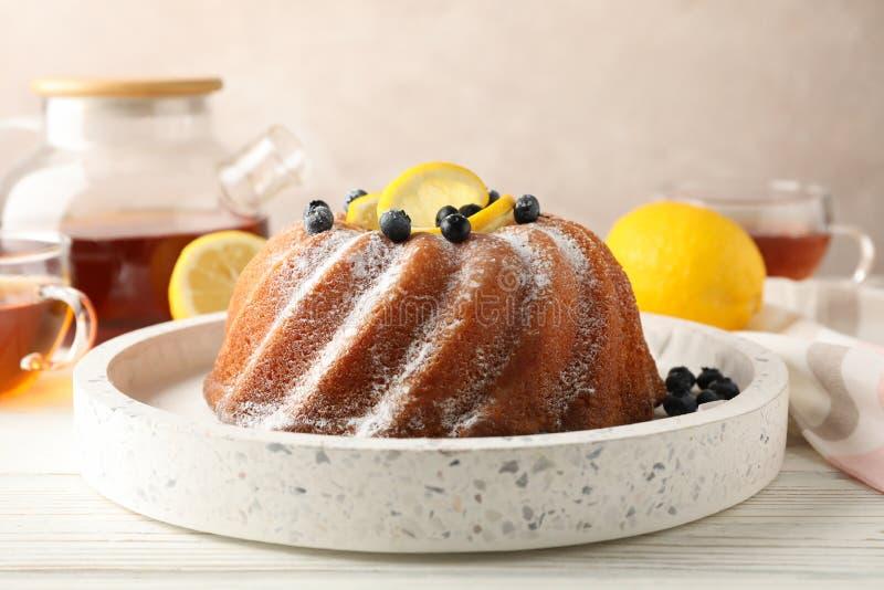 Cake with powder sugar and lemon on white background. Close up stock photo