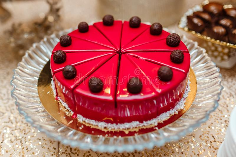 Cake in rode glans op lijst, besnoeiing in stukken verfraaid met chocoladeballen Suikergoedbar royalty-vrije stock afbeeldingen