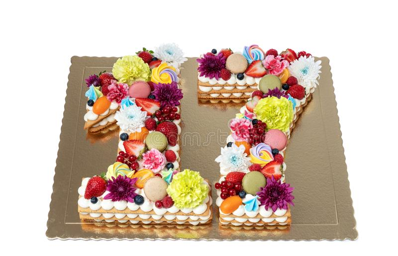 A cake in the shape of a figure sixteen of flowers and fruits. A cake in the shape of a figure sixteen of flowers and fruits stock photo