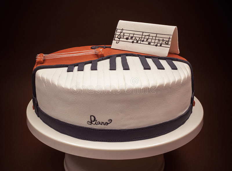 Cake In Shape of Piano and Cello. Birthday cake decorated with fondant, rounded, symbolically presenting piano and cello instruments royalty free stock photography