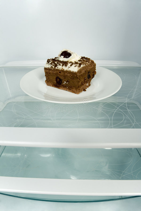 Cake on shelf. Piece of cake on dessert plate in fridge. Front view stock photos
