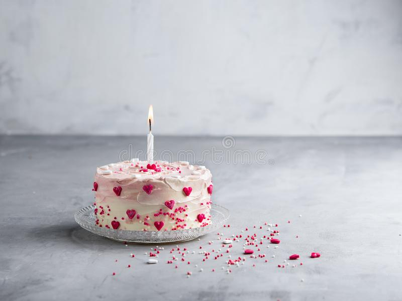 Cake with small hearts and colorful sprinkles with one candle on light background. Romantic love background. stock photos