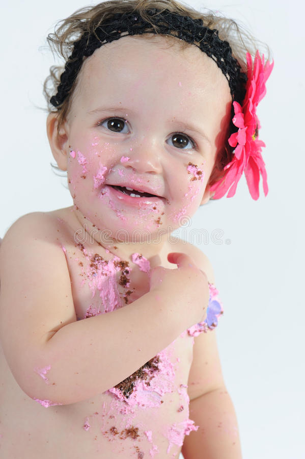 Cake smash shoot: Messy baby girl after eating birthday cake!. A happy baby girl after eating cake on her first birthday stock image