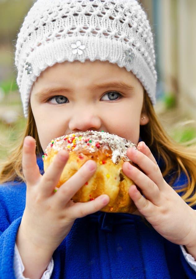 cake som äter flickan little utomhus- stående royaltyfri fotografi