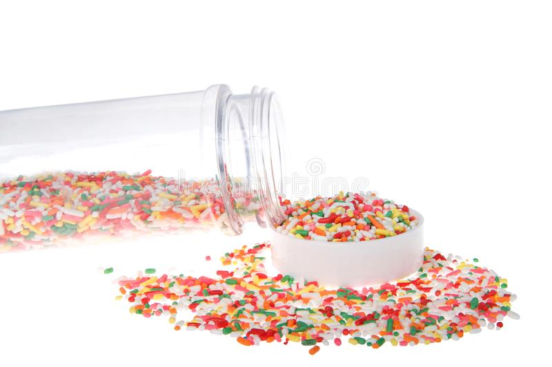 Cake sprinkles spilling onto cap and table isolated stock image