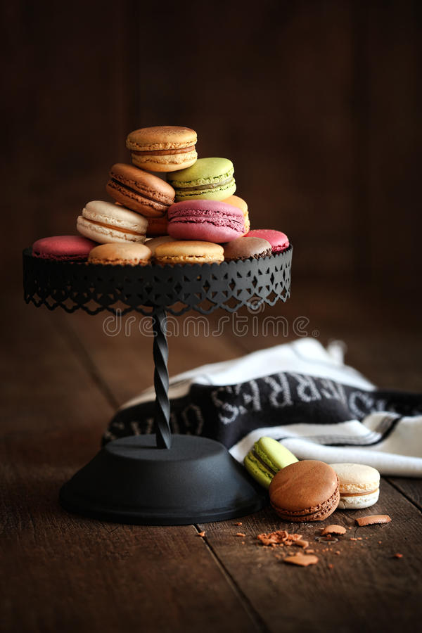 Cake stand with macaroons on dark wood background. Metal cake stand with macaroons on dark wood background stock image