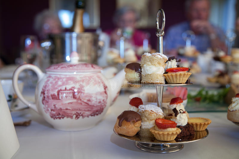 Afternoon tea. Cake stand with mini cakes on a table set for an afternoon tea party royalty free stock images