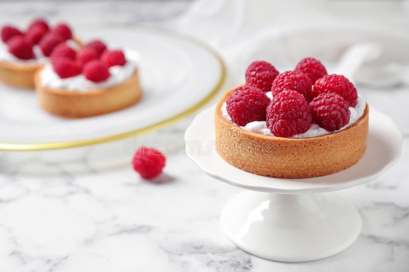 Cake stand with raspberry tart on marble table. Delicious pastries. Cake stand with raspberry tart on marble table, space for text. Delicious pastries royalty free stock image