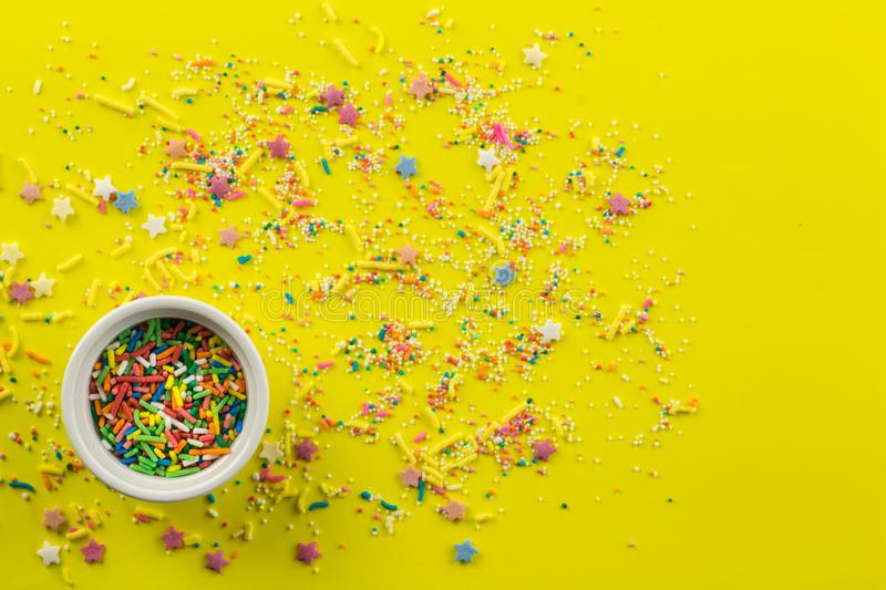 Cake topping prinkles on bright yellow background with little white bowl with various type of coloured sprinkles at bottom  and. Sprinkles on bright yellow royalty free stock image