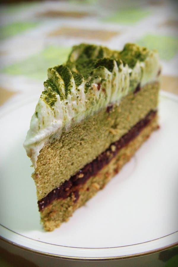 Cake van de Matcha de groene thee met slagroom en rood boondeeg royalty-vrije stock afbeelding