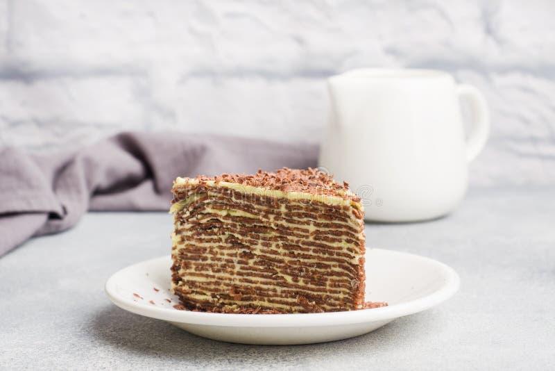 Cake van dunne chocoladepannekoeken en pistacheroom op een grijze achtergrond stock fotografie