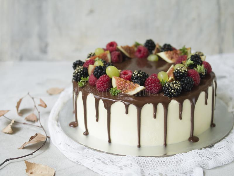 Cake with white cream, chocolate drips and seasonal berries and fruits: figs, grapes, raspberries and blackberries royalty free stock photos