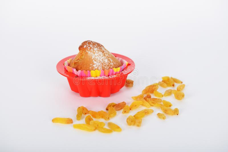 The cake with white sugar powder on it is in special form for cake cooking. And raisins stock image