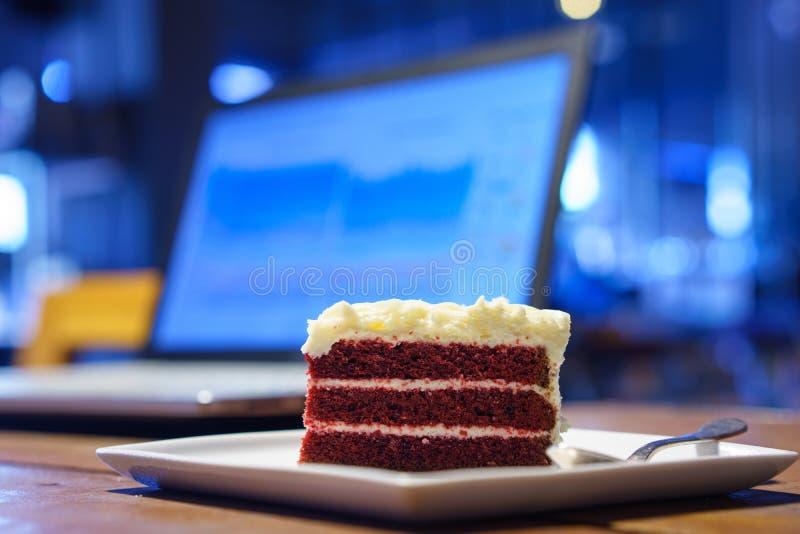 Cakechocolade op het houten lijstwerk met laptop notitieboekjecomputer royalty-vrije stock afbeelding