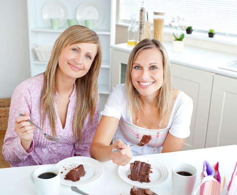 cakechoklad som äter eleganta kvinnor royaltyfri fotografi