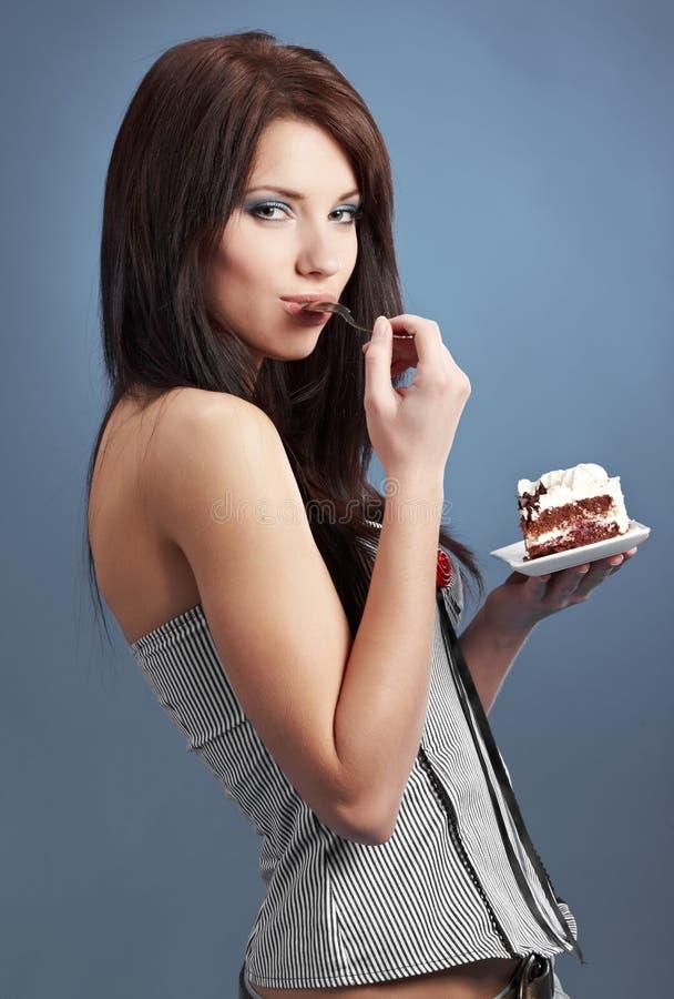 caken äter den söta kvinnan för skivan royaltyfria bilder