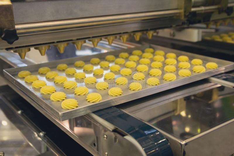 Cakes on automatic conveyor belt or line, process of baking in confectionery factory stock photos