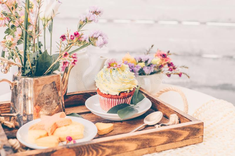 Cakes on beautiful wooden tray with flowers stock photo