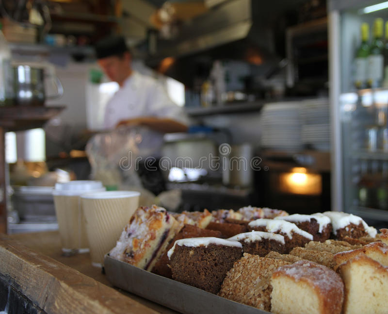 Cakes in cafe on Thurlestone Beach, Devon. Cakes in cafe on Thurlstone Beach, Devon. Blurred chef a cake varieties in focus with cafe interior out of focus royalty free stock photos