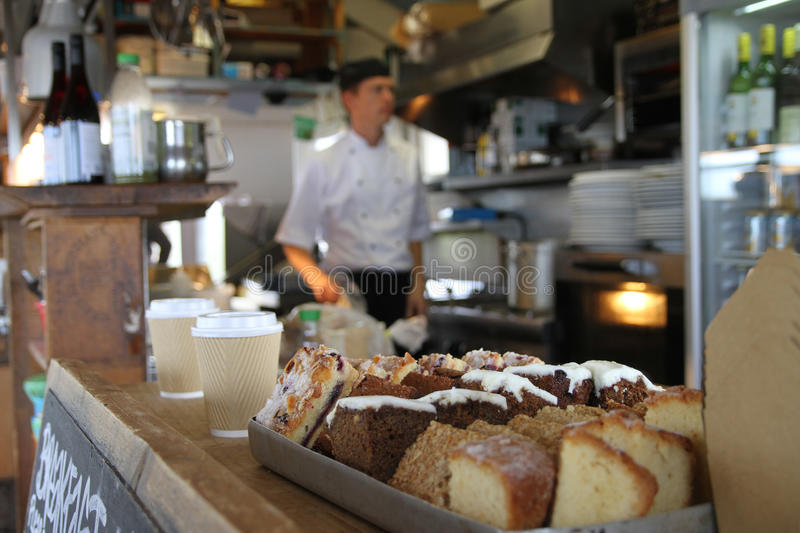Cakes in cafe on Thurlstone Beach, Devon. Blurred chef a cake varieties in focus with cafe interior out of focus stock images