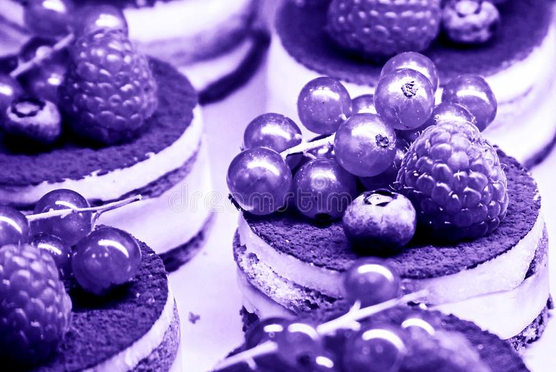 Cakes with cream and berries. Cakes with cream and fresh berries in ultra violet color of 2018 concept royalty free stock photos