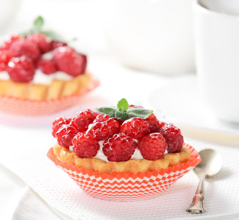 Cakes with cream, and juicy ripe raspberries, a teaspoon on a light background. Cakes with cream and juicy ripe raspberries on light background royalty free stock image