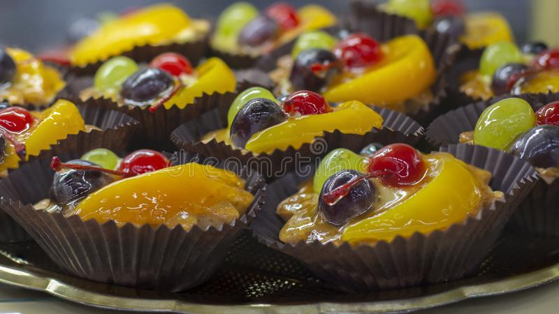Cakes fruit basket on the window of a pastry shop, close-up. Fruit in jelly in shortcrust pastry stock image