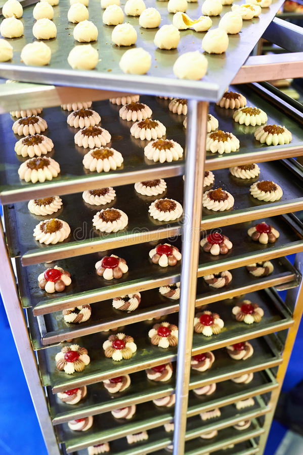 Cakes on metal shelves in confectionery factory. Cakes on metal shelves in a confectionery factory royalty free stock image