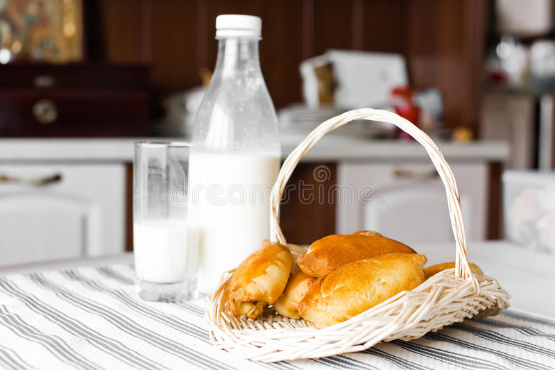 Cakes with milk. Cakes on basket with cup milk on table royalty free stock photo