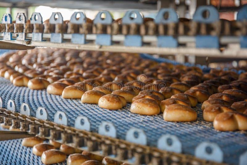 Cakes op geautomatiseerd om transportbandmachine in de fabriek van het bakkerijvoedsel, productielijn stock afbeeldingen