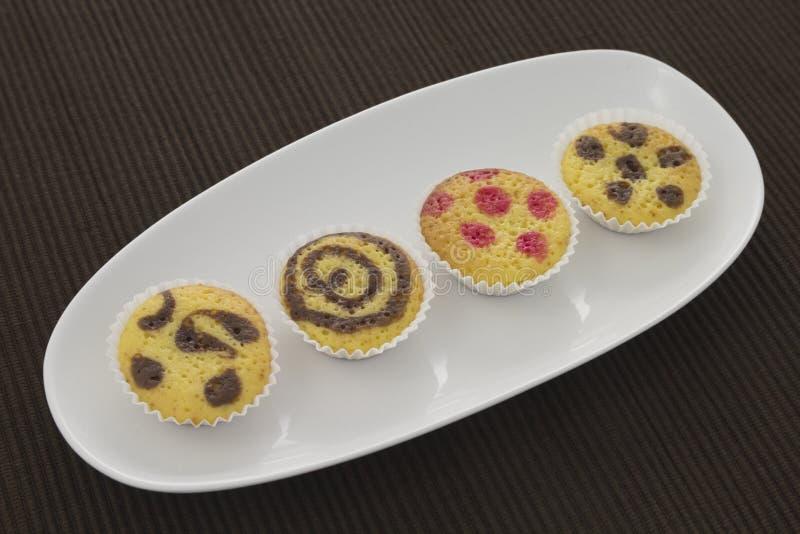 Cakes på en platta över den bruna handduken fotografering för bildbyråer