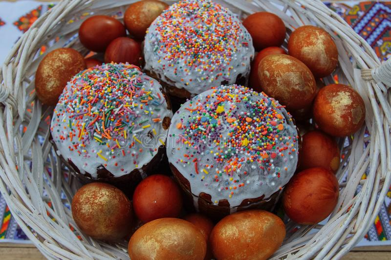 Cakes and painted eggs in a white basket stock image