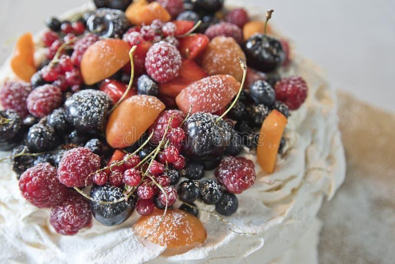 Cakeschuimgebakjes met vruchten en bessen Bessen, kersen, frambozen en abrikozen royalty-vrije stock foto