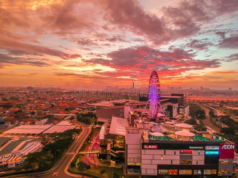 Cakung, East Jakarta, Indonesien (02/Mei/2019) : Aeralvy av solnedgången med färgade moln vid Eon Mall JGC fotografering för bildbyråer