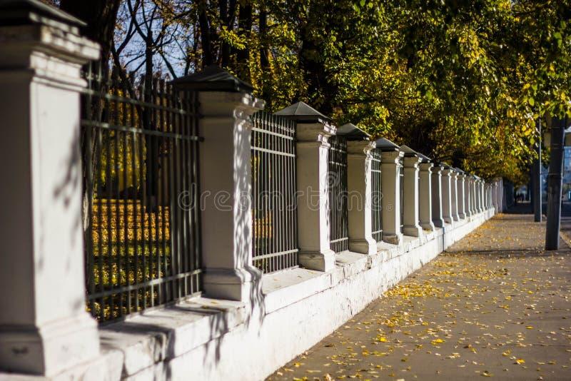 Calçada ao longo da cerca de pedra branca com barras pretas no fundo da paisagem do outono. beco da cidade no outono fotografia de stock
