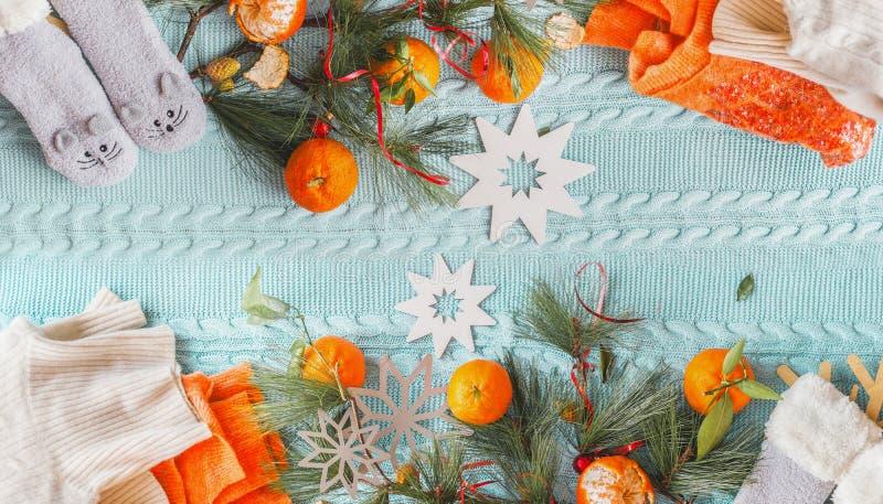 Calçado, no inverno, com tangerinas, suéter de laranja, meias engraçadas e ramos de abeto em cobertor de malha azul com flocos de fotos de stock royalty free