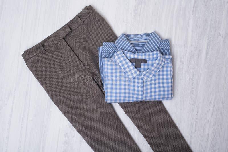 Calças cinzentas e camisas azuis no fundo de madeira Engodo elegante fotografia de stock