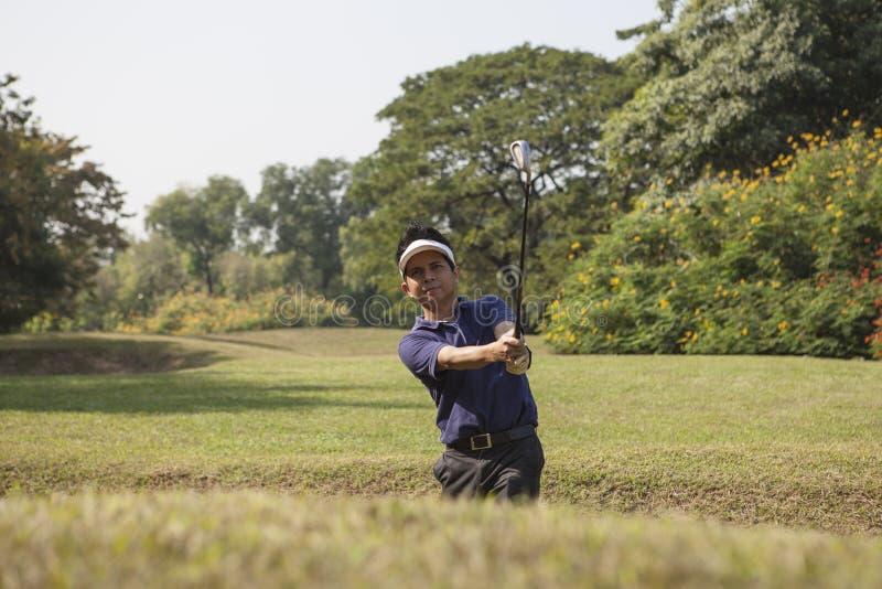 Calças cinzentas masculinas novas do jogador de golfe que lascam a bola de golfe fora de um sa imagem de stock