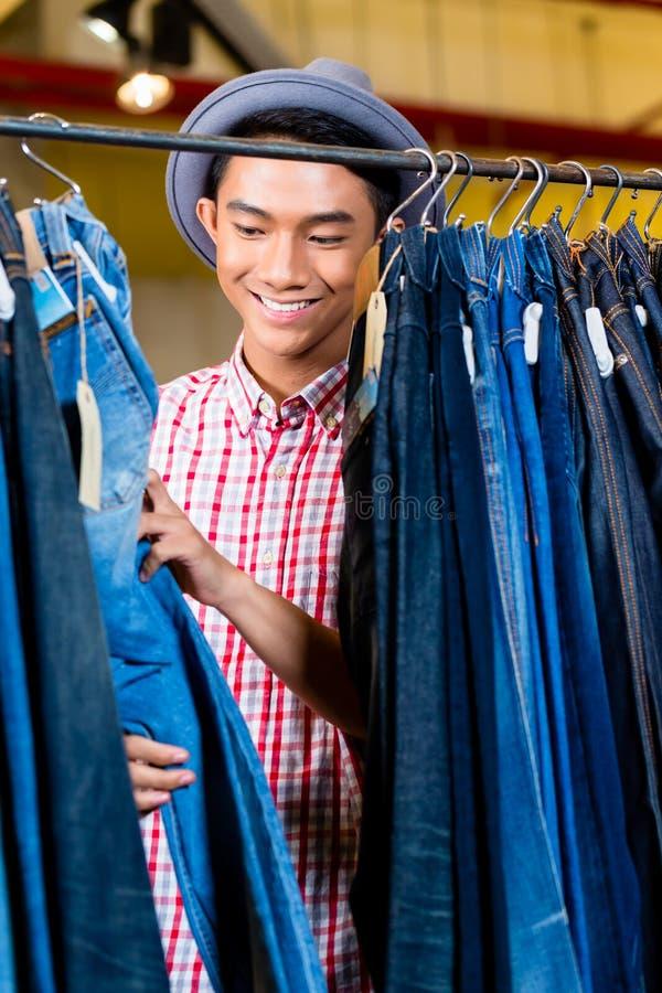 Calças de brim asiáticas da consultação do homem na loja da forma fotografia de stock royalty free