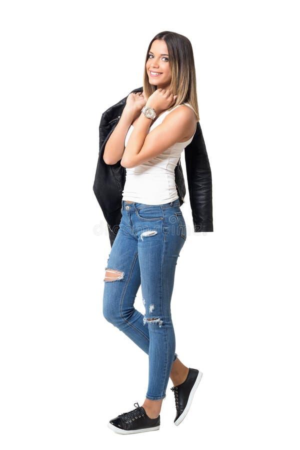 Calças de brim, camiseta de alças, casaco de cabedal moderno e sapatilhas vestindo do modelo de forma levantando na câmera fotografia de stock royalty free